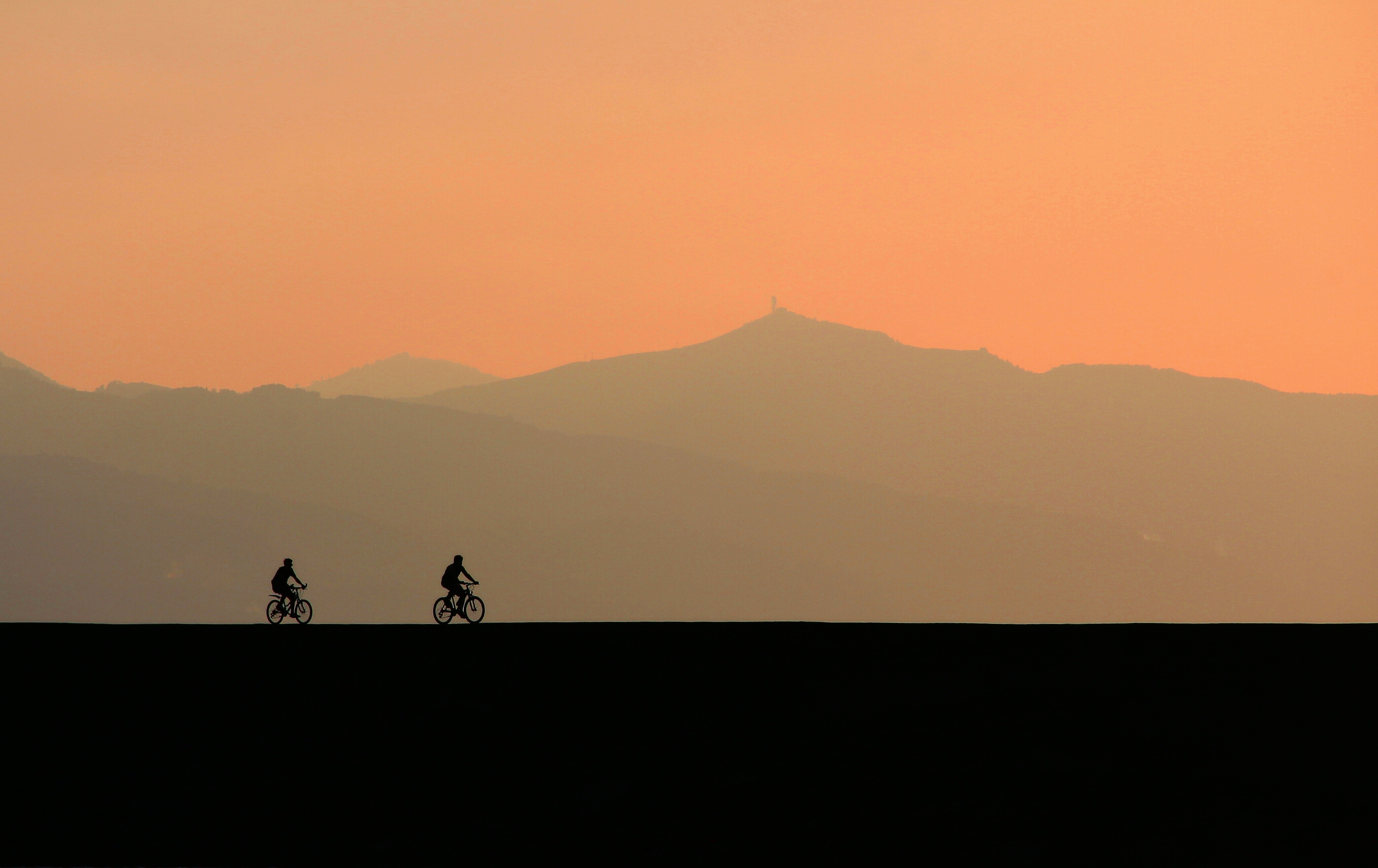 two men cycle backlit by the setting sun