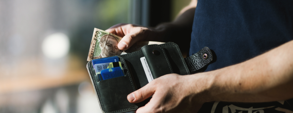 man reaches into his wallet for debit card